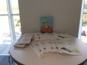Table with flyers and Dr. Suess book for children's story hour at Map Mosaic: From Queens to the World, Queens Museum, NY
